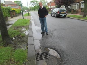 Cllr Mike Carling inspects potholes in Borough Road